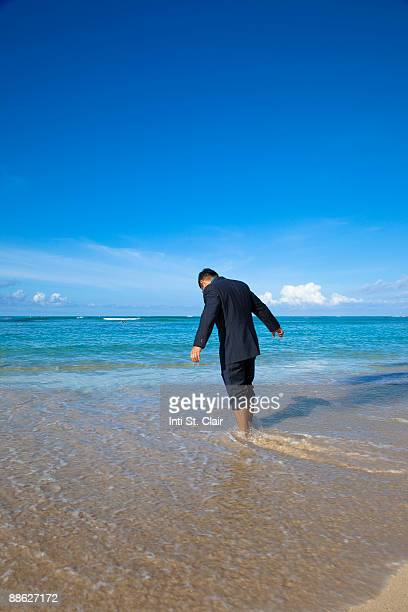 man in business suit standing on beach - rolled up trousers stock pictures, royalty-free photos & images