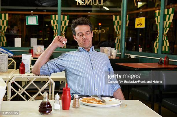 Man in cafe with empty plate