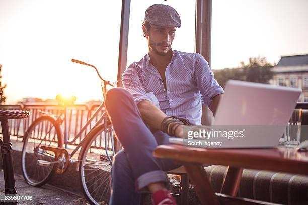 Man in cafe works on laptop