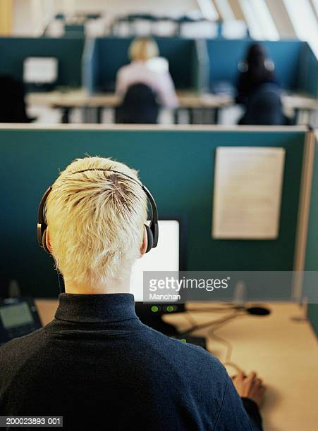 Man in call centre, wearing headset, rear view