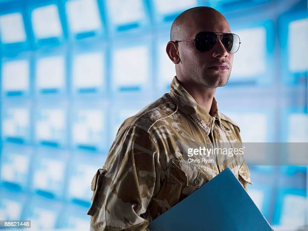 man in camouflage holding folder near bank of computers - central intelligence agency stock pictures, royalty-free photos & images