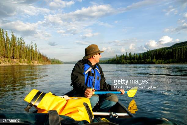 man in canoe on yukon river against sky - monika gregussova stock pictures, royalty-free photos & images