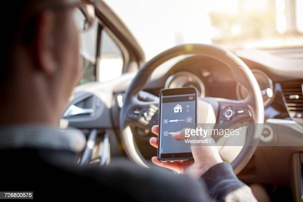 Man in car adjusting devices at home via smartphone
