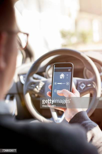 man in car adjusting devices at home via smartphone - transportation occupation stock pictures, royalty-free photos & images