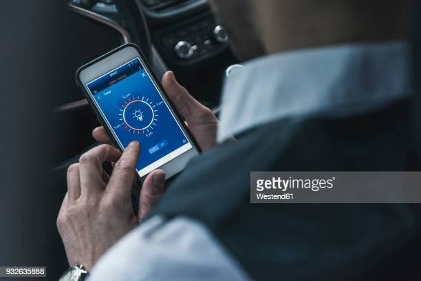 Man in car adjusting smart home device via smartphone