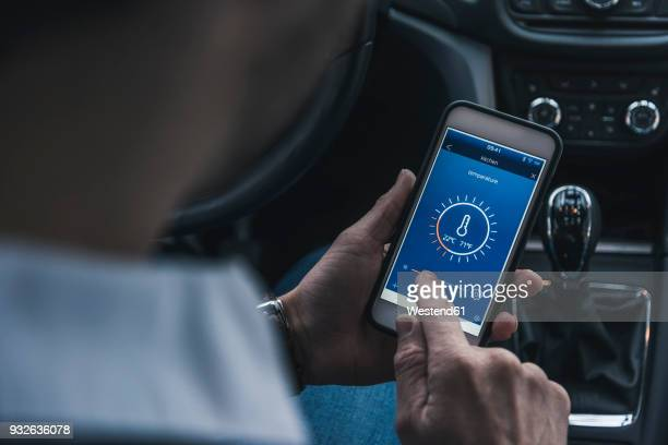 man in car adjusting smart home device via smartphone - smart stock pictures, royalty-free photos & images