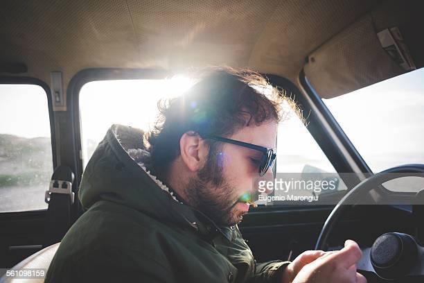 Man in car at beach rolling a cigarette