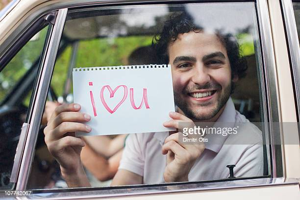 man in car holding sign saying 'i love you' - i love you photos et images de collection