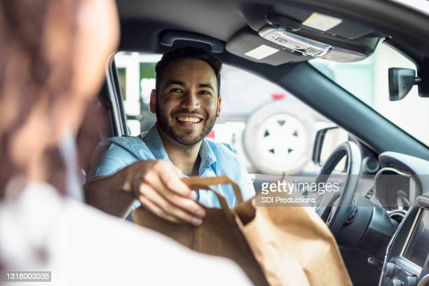 man in car smiles while taking food order from woman - curbside pickup stock pictures, royalty-free photos & images