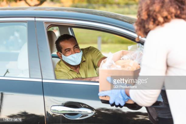 man in car wears mask while receiving box of food - food bank stock pictures, royalty-free photos & images