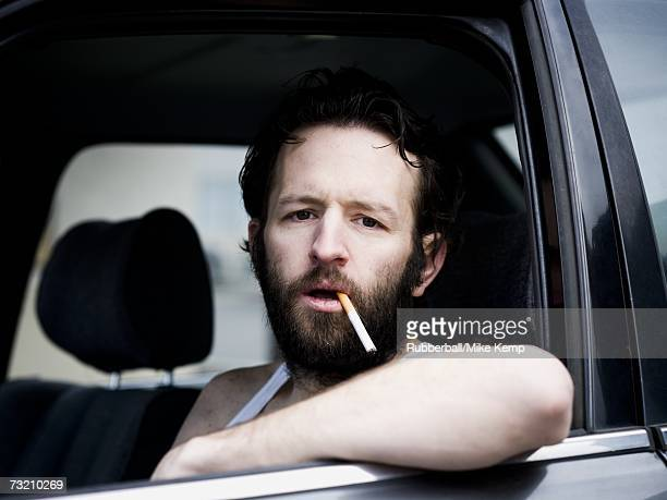 man in car with cigarette hanging from mouth - hillbilly stock pictures, royalty-free photos & images