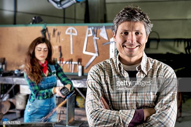 Mann in Tischlerarbeit. Arbeiter Frau hinter ihm.