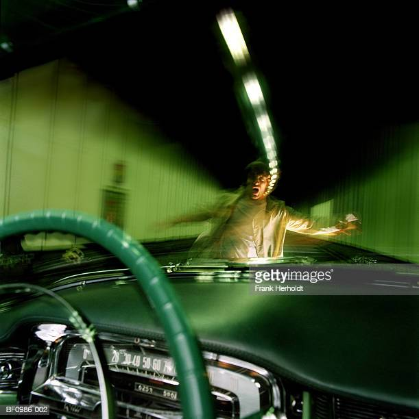 Man in centre of road, view from inside car (blurred motion)