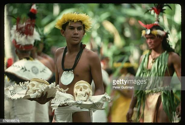 Man in Ceremony Carries Human Skulls