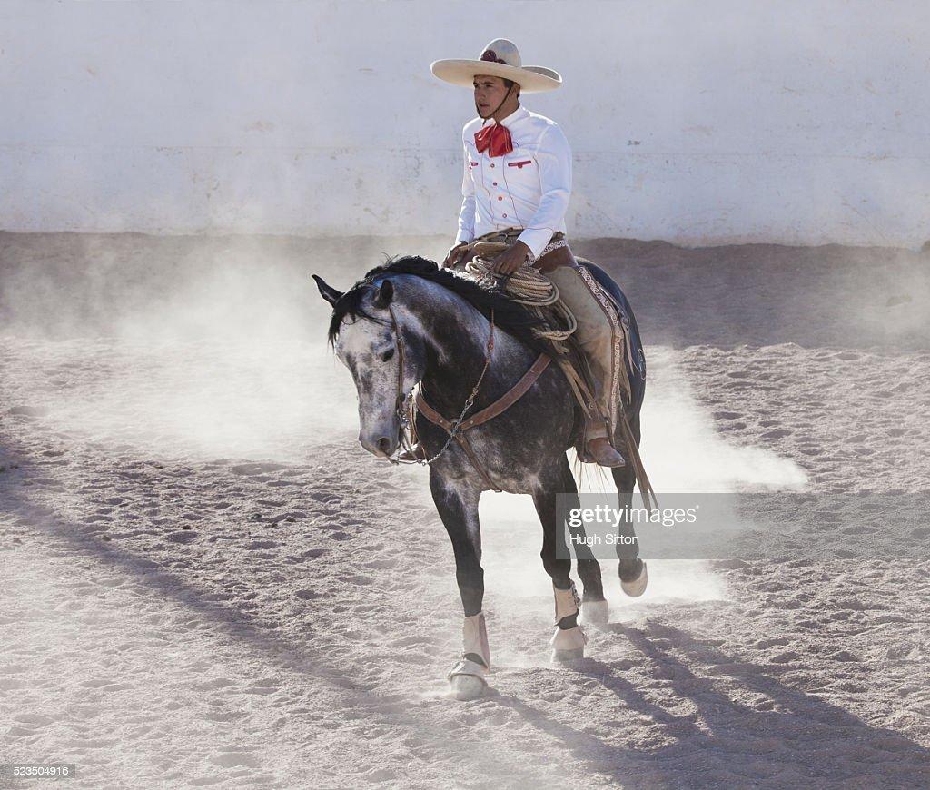Man in charro costume riding horse : Stock Photo