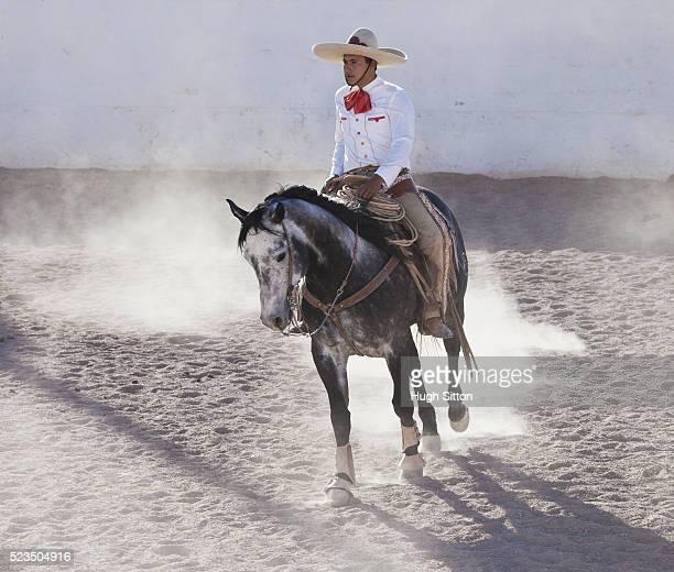 man in charro costume riding horse - hugh sitton photos et images de collection