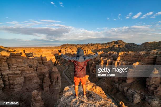 man in charyn canyon with sunset, kazakhstan - kazakhstan stock pictures, royalty-free photos & images