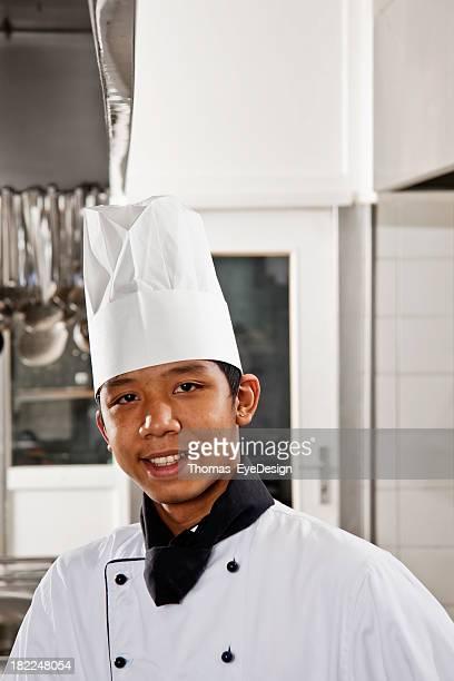 man in chef uniform posing in kitchen