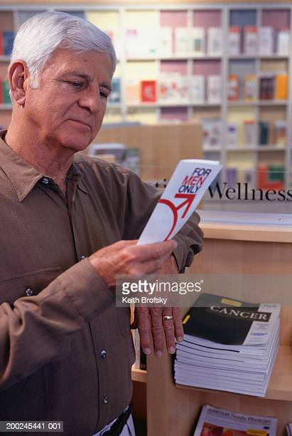 Man in chemist looking at prostate brochure