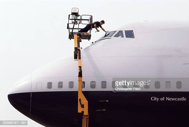 Man in cherry picker cleaning windscreen of commercial plane,side view
