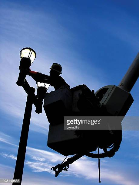 Man in Cherry Picker Fixing Lights
