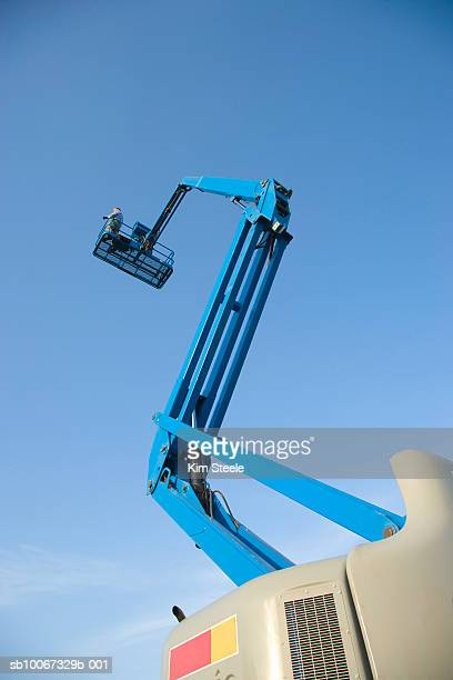 Man in cherry picker, low angle view