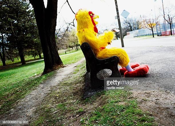Man in chicken suit sitting on park bench reading newspaper