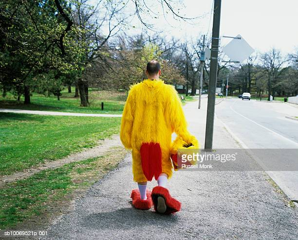 Man in chicken suit walking in park, rear view