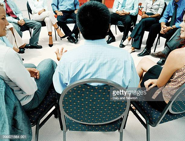 Man in circle of people addressing colleagues, rear view