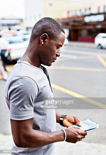 man in city street with new south african mandela banknotes - south african currency stock photos and pictures