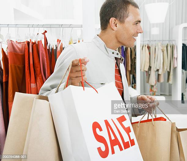 man in clothes shop carrying 'sale' bags, smiling, profile - medium group of objects stock pictures, royalty-free photos & images
