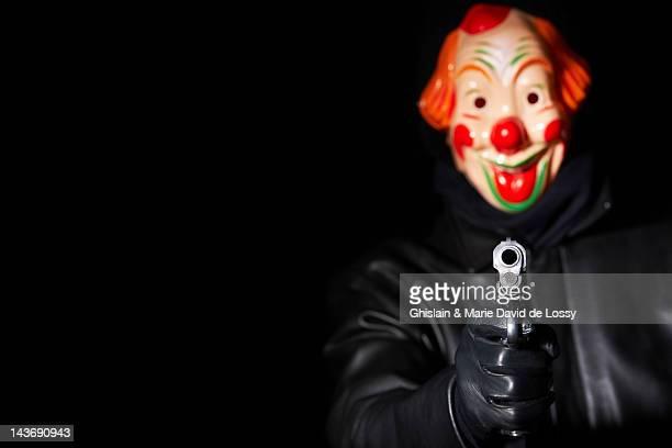 Man in clown mask pointing gun
