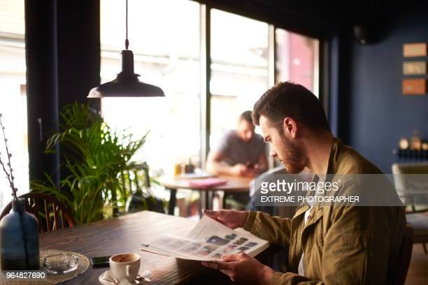 man in coffee shop - magazine stock pictures, royalty-free photos & images