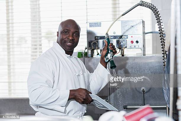 Man in commercial kitchen at sink cleaning dishes