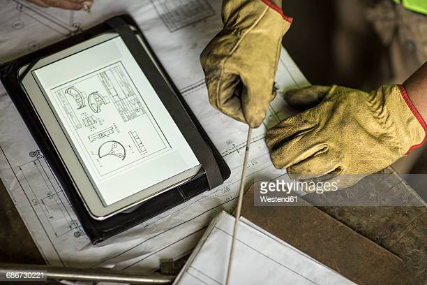 man in construction company working with blueprint on digital tablet - work glove stock pictures, royalty-free photos & images