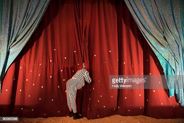 man in costume peeking through stage curtain - stage curtain stock pictures, royalty-free photos & images