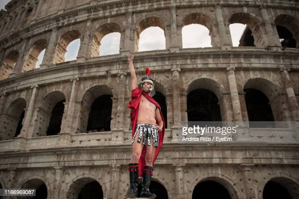 man in costume standing against coliseum - andrea rizzi - fotografias e filmes do acervo