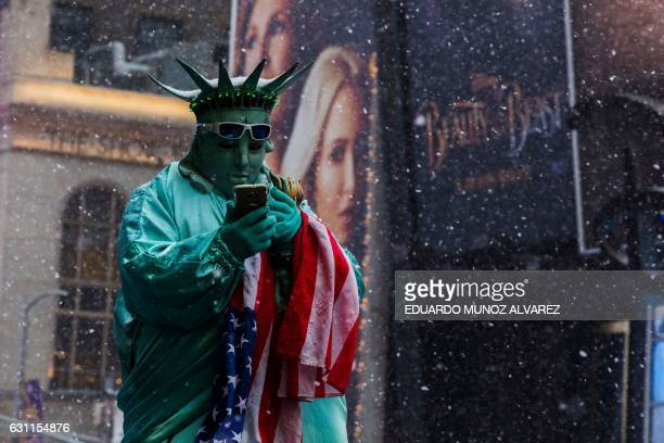 A man in costume waits for tourists to take picture with him under a snowfall in Times Square during a winter storm on January 7 2017 in New York /...
