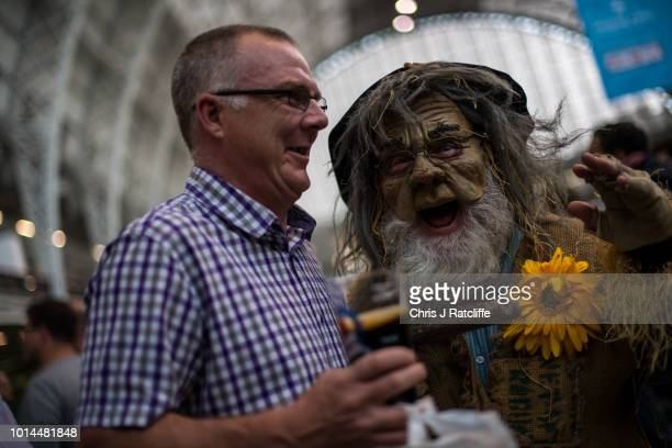 A man in costume walks amongst beer enthusiasts during the Great British Beer Festival at Olympia Exhibition Centre on August 10 2018 in London...