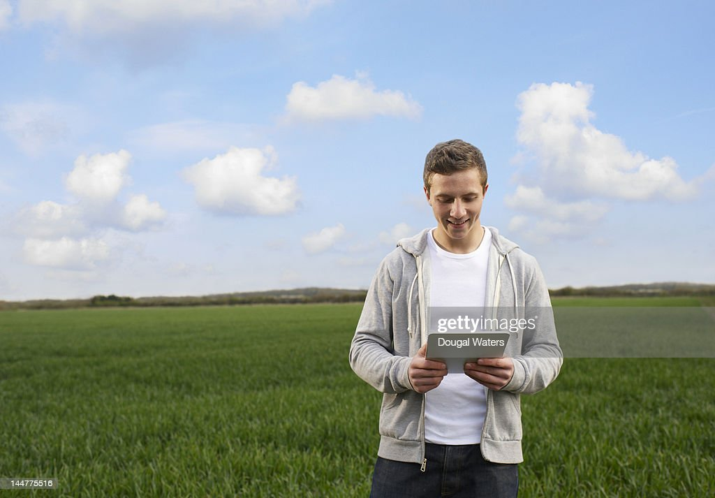 Man in countryside using digital tablet. : Stock Photo