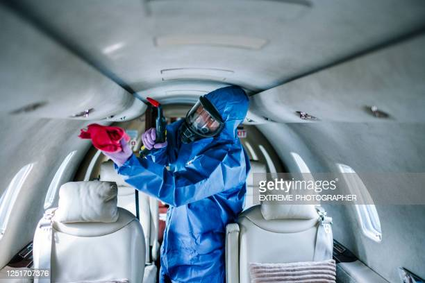 a man in coveralls cleaning seats in a private airplane during a covid-19 pandemic - department of health stock pictures, royalty-free photos & images