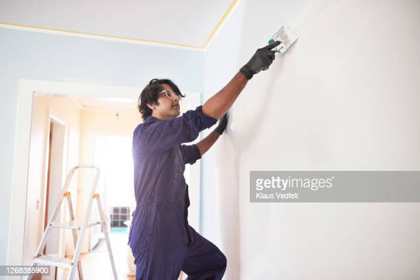 man in coveralls renovating home - glove stock pictures, royalty-free photos & images