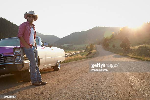 Man in cowboy hat, leaning against convertible car