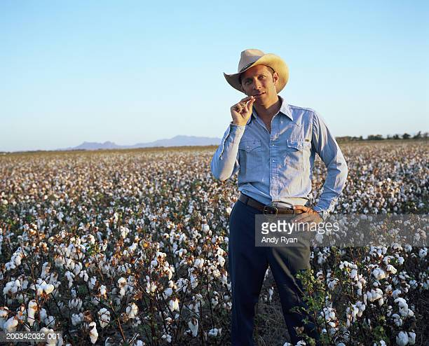 Man in cowboy hat standing in cotton field, portrait, close-up