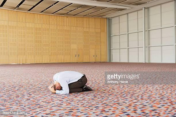 Man in cradling head kneeling on floor in empty conference hall