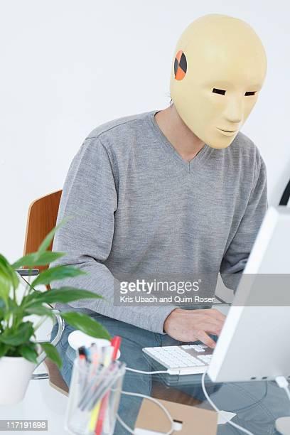 Man in crash dummy mask working at computer