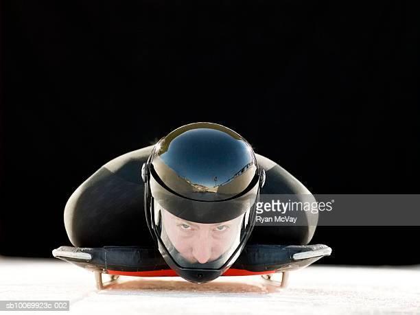 Man in crash helmet on skeleton sled, portrait, close-up.