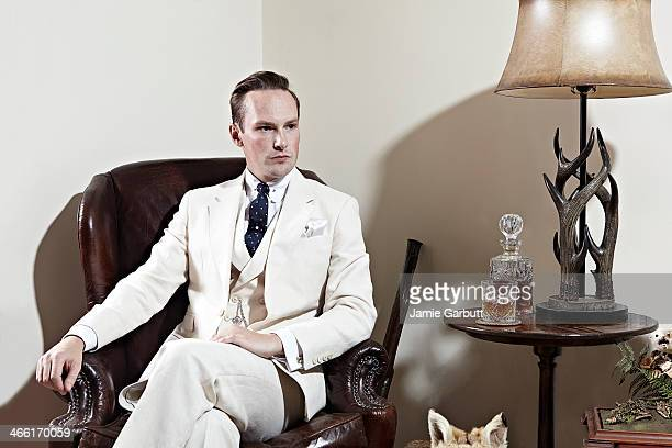 Man in cream suit sitting in chair with whisky.