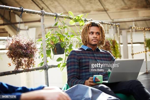 Man in creative office environment during an informal meeting on a laptop.