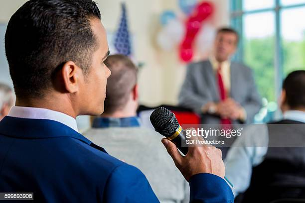 man in crowd asking question during town hall meeting - town hall meeting stock photos and pictures